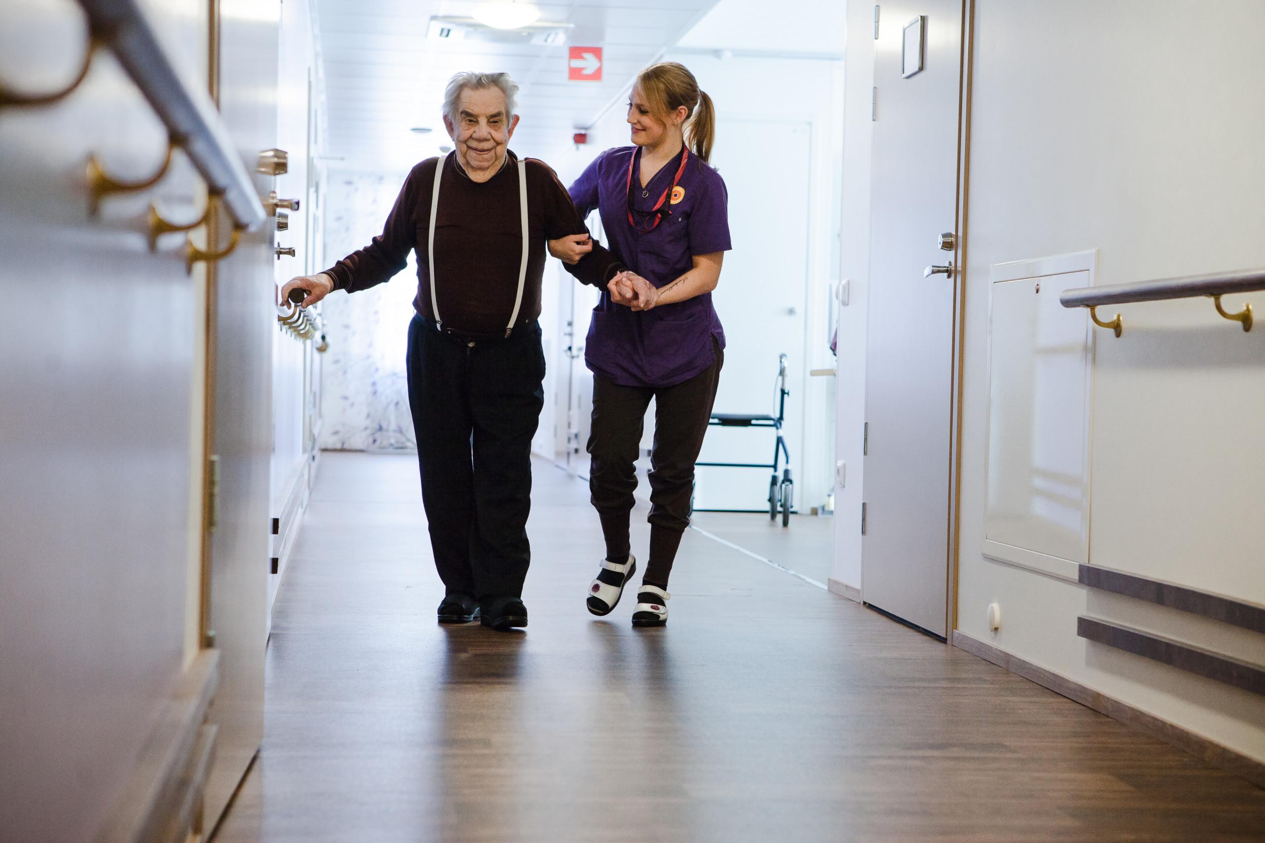 Iäkäs mies kävelee käytävällä hoitajan avustamana.
