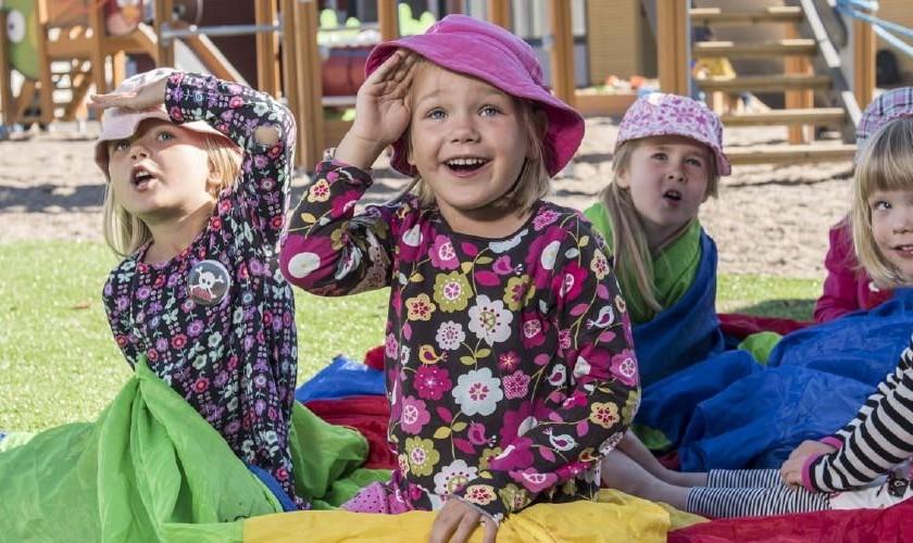 Lapset istuvan pihalla värikkään kankaan päällä ja katsovat kameran yli