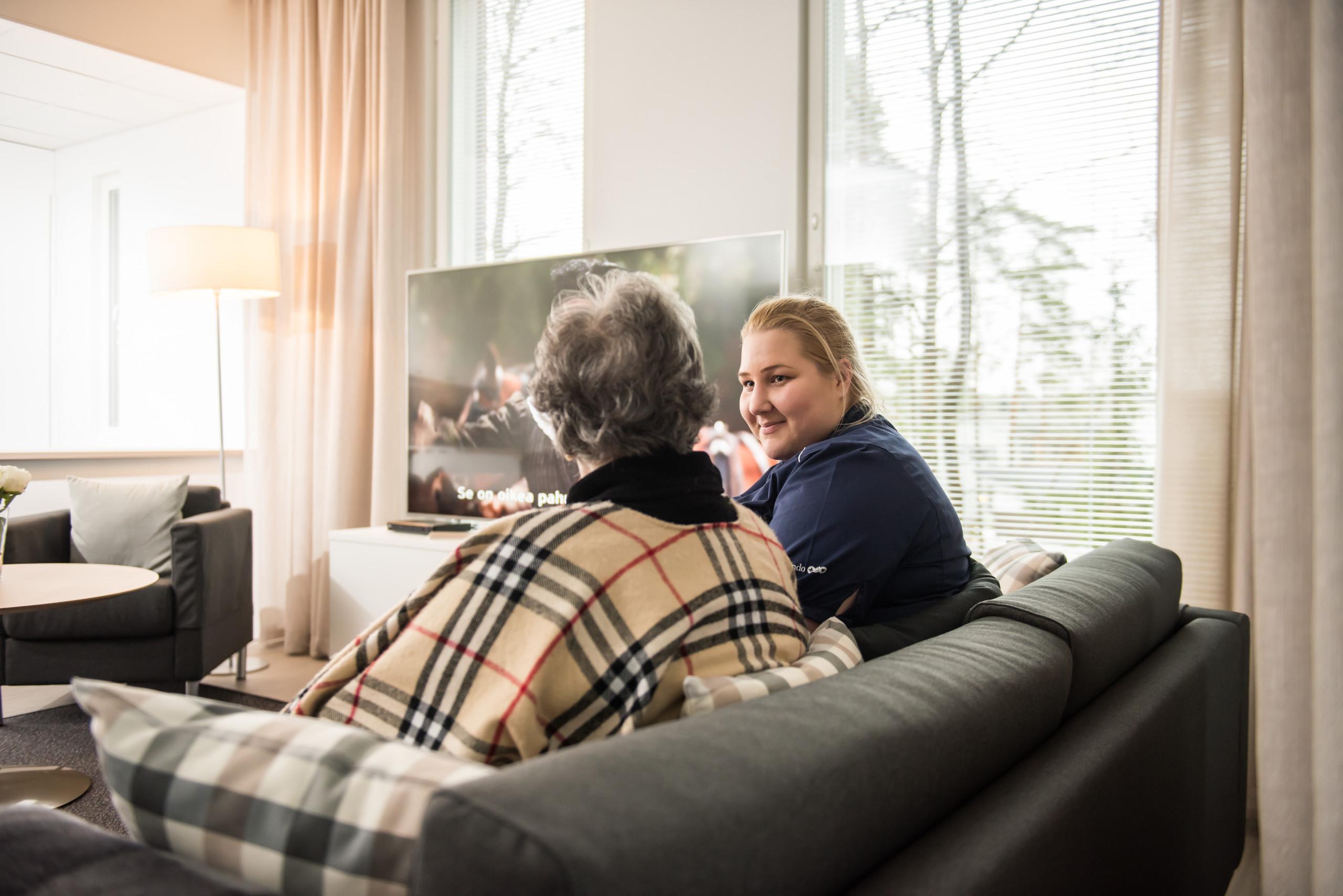 Hoitaja ja iäkäs nainen istuvat sohvalla keittiössä.
