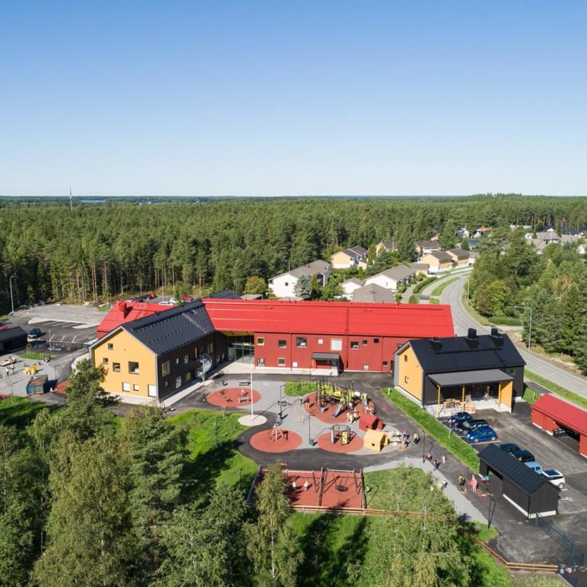 Punakattoinen rakennus kuvattuna ylhäältä päin.