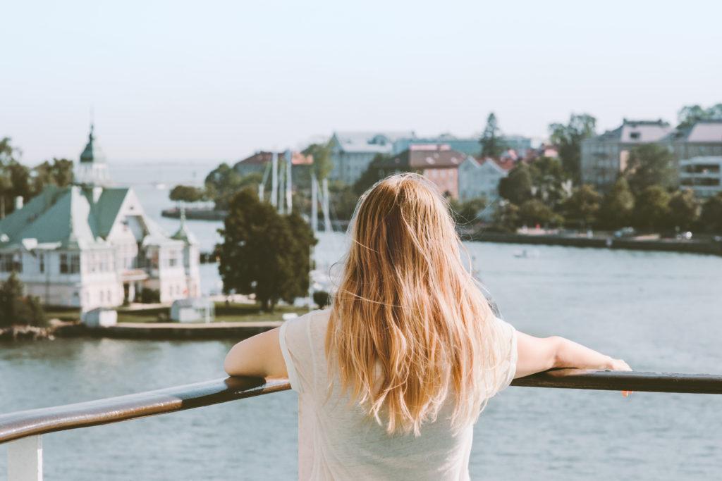 Nainen katselee maisee merelle päin.