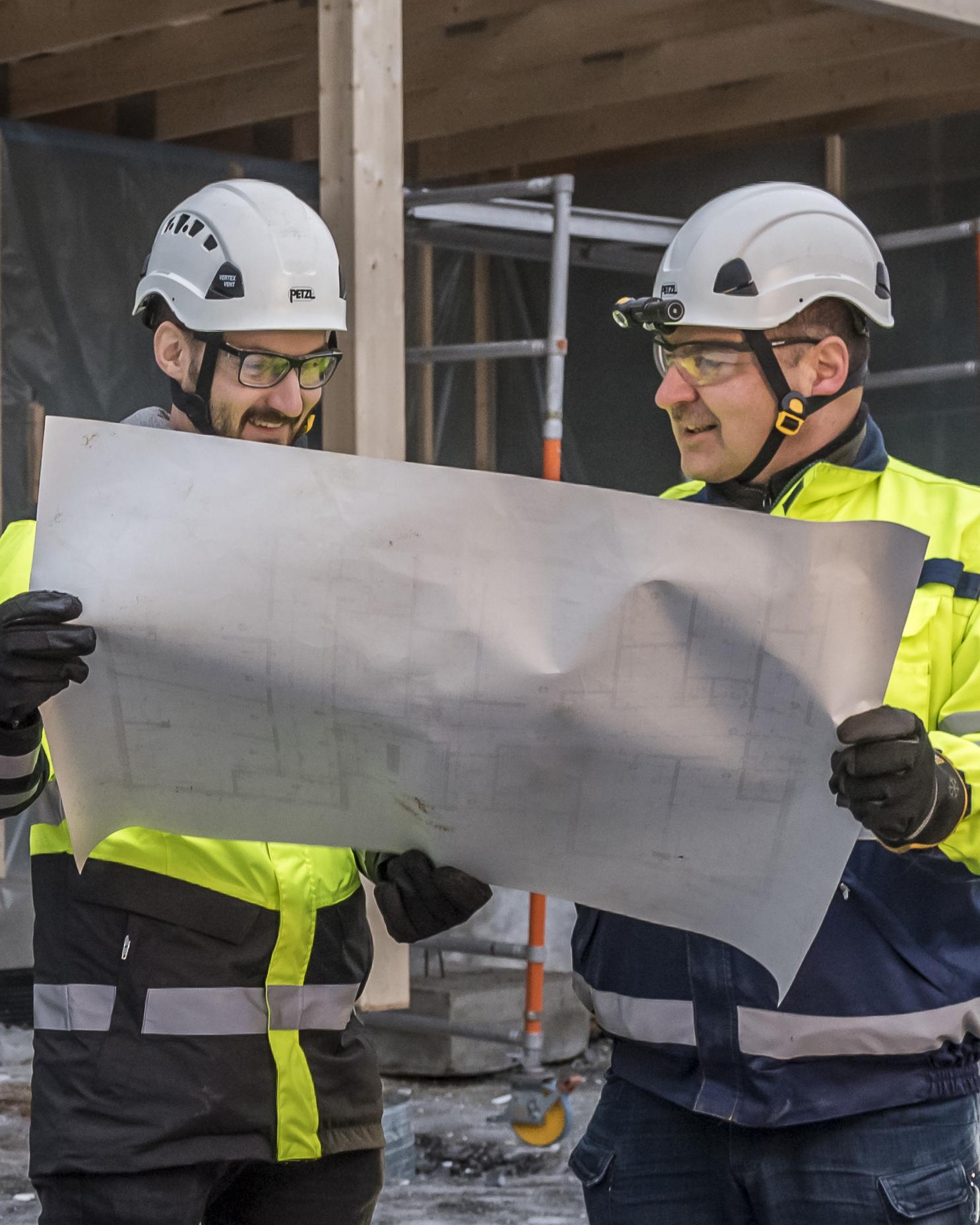 Kaksi työasuista miestä lukee suunnitelmaa rakennustyömaalla.