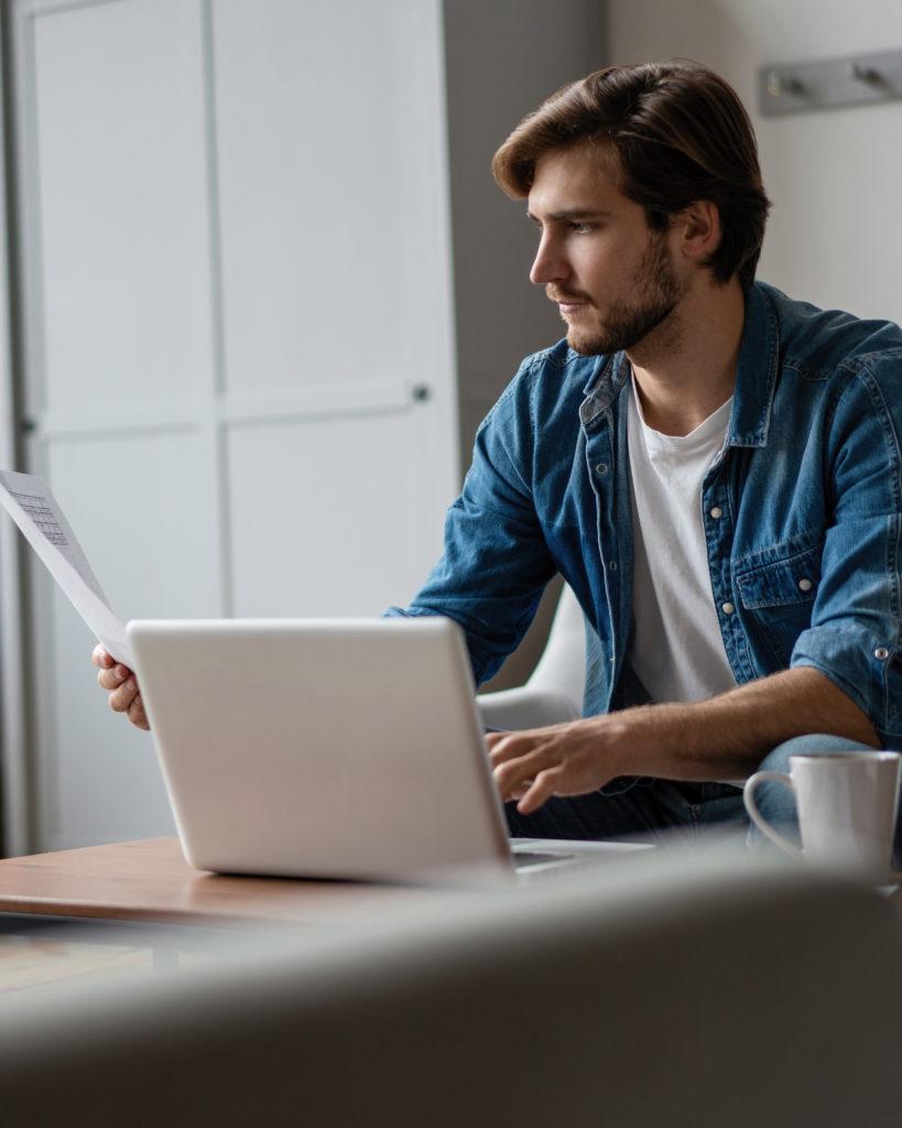 Mies kannettavalla tietokoneella paperin kanssa.