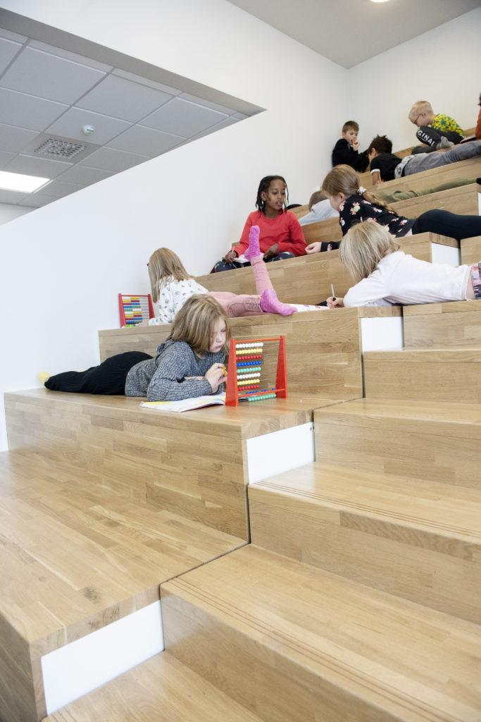 Lapsia helmitaulujen kanssa portaikossa.