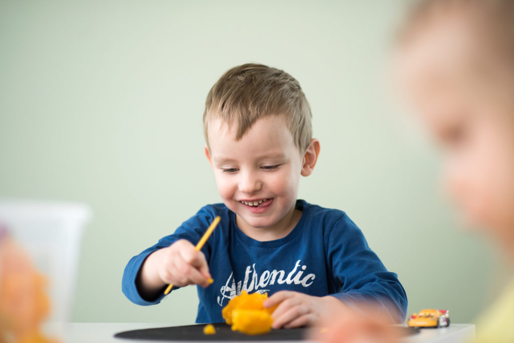 Poika askartelee pöydän ääressä kieli poskessa.